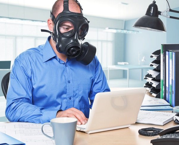 man wearing gas mask work with laptop